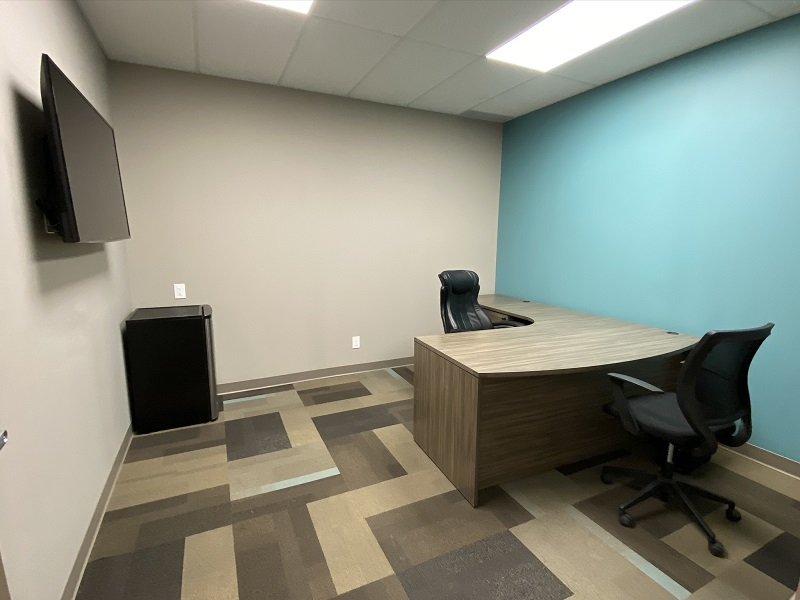 Desk  and mini-fridge view of Office 34 in the EYE For Business Center